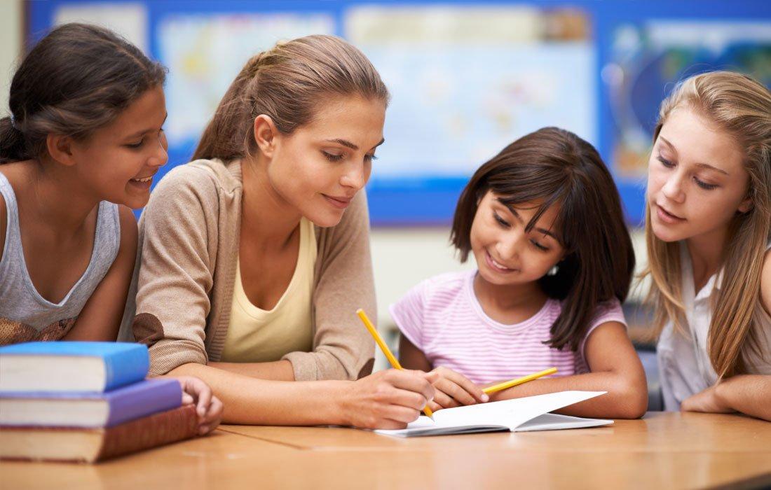 Immagine che raffigura un esempio di inclusione in classe e di lavoro di gruppo: la maestra e delle bambine scrivono insieme su un quaderno
