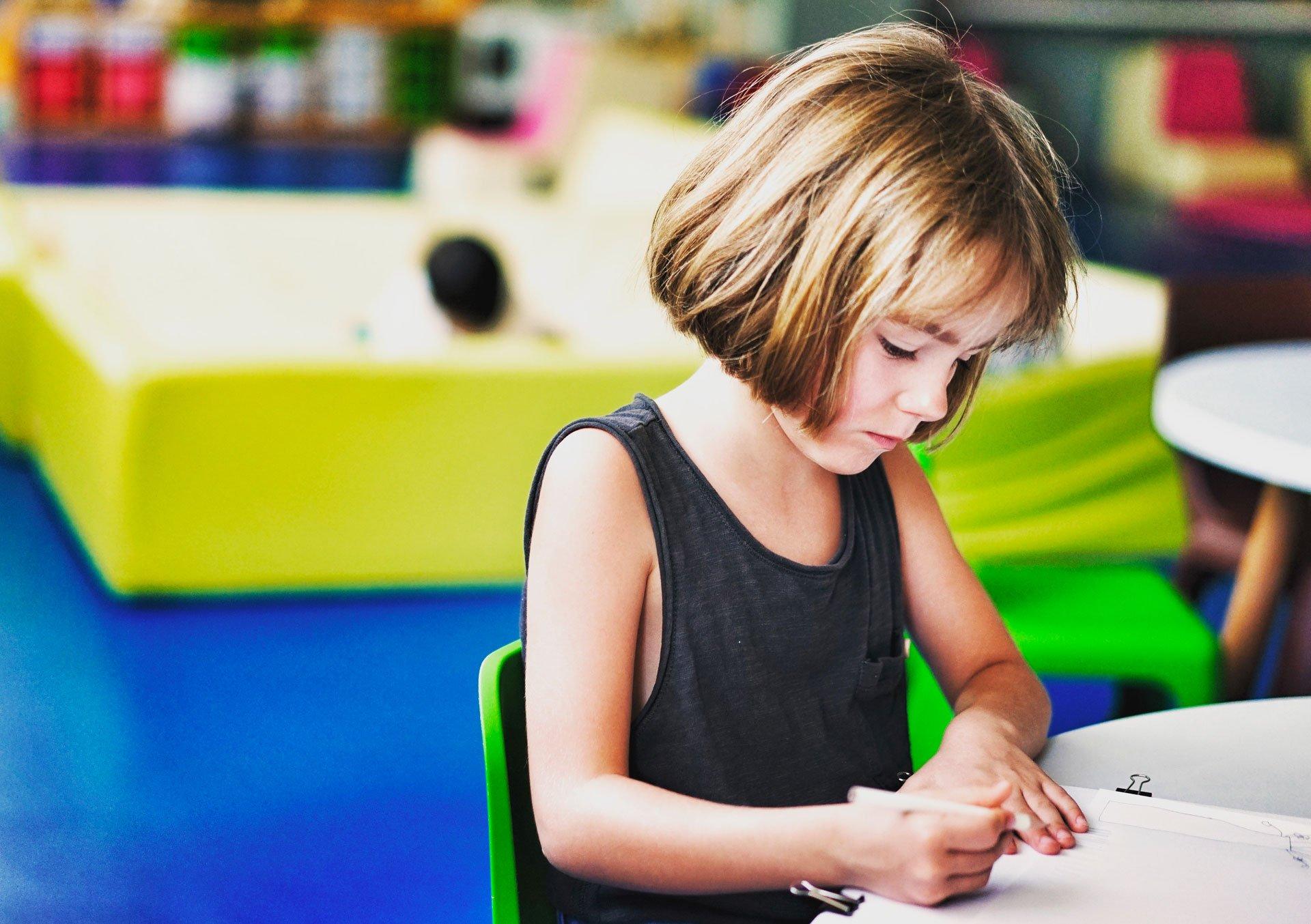 L'immagine rappresenta una bambina, sola in aula, che scrive